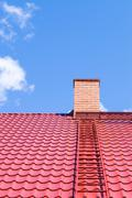 Brick chimney on red roof with metal ladder Stock Photos