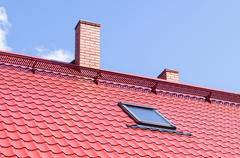 Brick chimney on red roof with mansard window Stock Photos