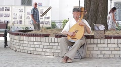 Man playing the harp in the courtyard of the church. Stock Footage