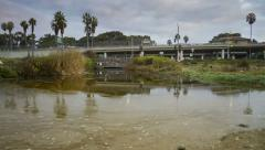 Stock Video Footage of 1080p Sunrise time lapse runoff beach water near freeway in California