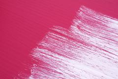 Brush strokes of white paint across a pink surface - stock photo