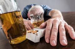 Drunk man slumped on table - stock photo