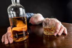 Drunk man slumped on table - stock photo