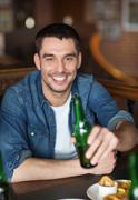 Stock Photo of happy young man drinking beer at bar or pub