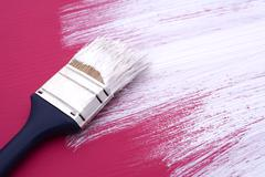 Dirty paintbrush with white paint on half-painted board Stock Photos