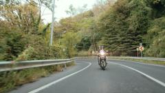 Young couple riding motorbike follows camera on country road - stock footage