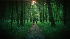 Man and Woman Walking as Couple in Dark Forest Stock Footage