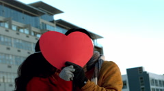 Romantic couple hiding themselves behind heart shape Stock Footage