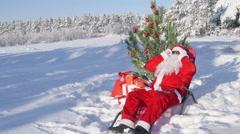 Santa Claus near Christmas tree enjoying frosty sunny day in snow Stock Footage