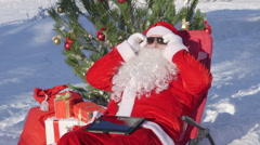 Santa Claus near Christmas tree in snow covered winter forestt - stock footage