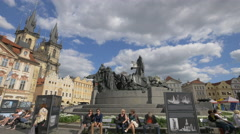 Tourists sitting near Jan Hus Memorial in Old Town Square, Prague Stock Footage