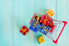 Cart with gifts on wooden background - stock photo