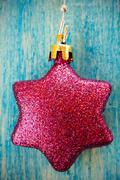 Stock Photo of Christmas bauble hanging on wooden background