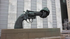 A gun sculpture with a twisted barrel sits outside the United Nations Building - stock footage
