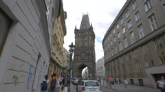 People passing near cars parked on Celetna street and the Powder Tower in Prague Stock Footage