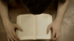 Omnipotent point of view of a young adult reading a book with Rack Focus Stock Footage