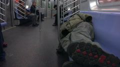 A homeless man sleeps in a subway train. Stock Footage