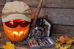 Halloween pumpkin in hat with fly-fishing tackles Stock Photos