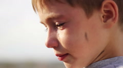 Dirty orphan boy closeup crying flowing tears Stock Footage