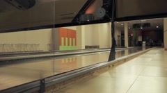 Bowler rolls bowling ball down a lane Stock Footage