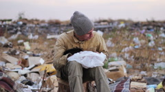 dirty homeless man sits on a stump in the trash and eat the food from the bag - stock footage