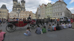 Tourists sitting down and watching a carriage in Old Town Square, Prague Stock Footage