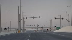 Unfinished highway, road to nowhere in desert, cyclist Stock Footage