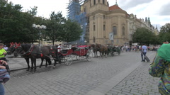 Tourists passing by two carriages with horses near St. Nicholas Church, Prague - stock footage