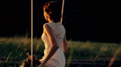 Beautiful young couple bride and groom in a wedding dress on a swing in the park - stock footage