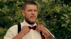 Groom wears a tie in the park at sunset Stock Footage