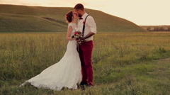 beautiful young couple bride and groom standing in the park at sunset - stock footage