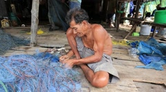 Old Thai man working with a fishing net in a fishing village, Thailand Stock Footage