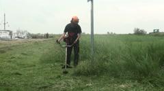 Grasscutting by handmachine. Stock Footage