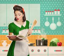 Young woman cooking and reading recipe cook book in her kitchen Stock Photos
