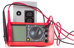 Stock Photo of Red multimeter and UPS (uninterruptible power supply)