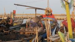 Men unloading small bright colored boat,Ceribon,Java,Indonesia Stock Footage