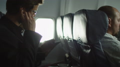 Young man is listening to music on an airplane and a woman is using tablet Stock Footage