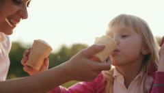 Family values: Mother and child eating ice cream at sunset. Close up - stock footage