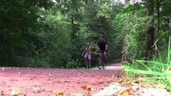 Cyclists in speed on a track landscaped in the woods - stock footage
