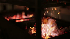 Stock Video Footage of Sparks fire cracks in grill fire pit.