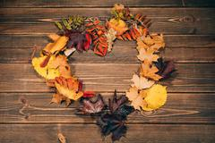 Background with wooden table and autumnal leaves - stock photo