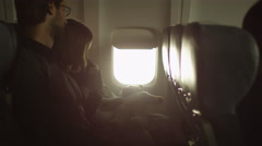Young family with a boy sit inside an airplane next to a window Stock Footage