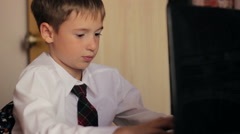 The little boy of 8 years in a white shirt and tie working on laptop computer Stock Footage