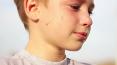 Dirty orphan boy close-up crying and looking at camera on the background of the Stock Footage