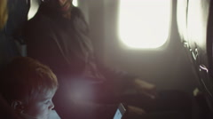Young boy is playing with tablet on an airplane while father talks to him Stock Footage