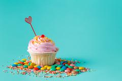 One cupcake on aquamarine background - stock photo