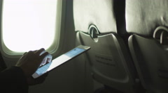 Young man in close-up is using a tablet inside an airplane next to a window Stock Footage