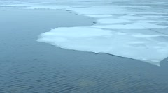 Melting floes of ice on water surface with small waves Stock Footage
