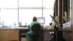 Nurse using computer, behind shot. Stock Footage