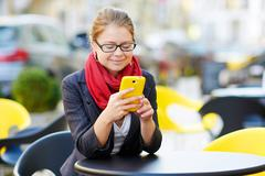 Young business woman is using smart phone for work in cafe - stock photo